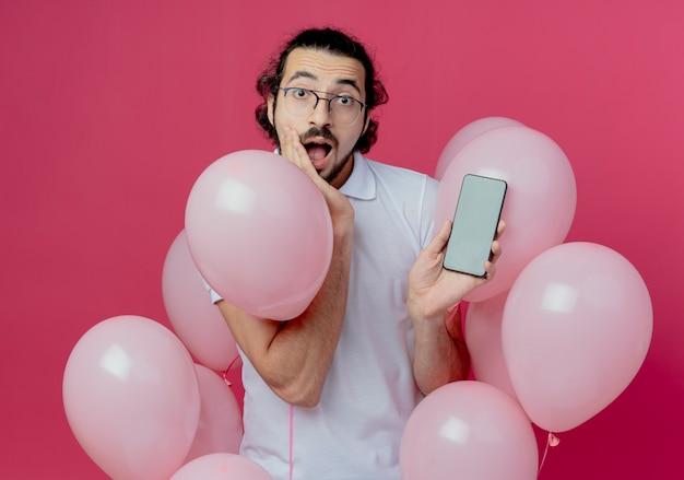 Uomo bello sorpreso con gli occhiali in piedi tra palloncini tenendo il telefono e mettendo la mano sulla guancia isolata sul muro rosa