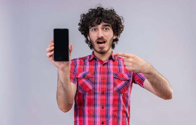 Un bell'uomo sorpreso con i capelli ricci in camicia a quadri che punta al cellulare con le dita