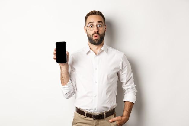 Удивленный красивый менеджер в очках, любопытно выглядящий и показывающий мобильный экран, стоя на белом фоне.