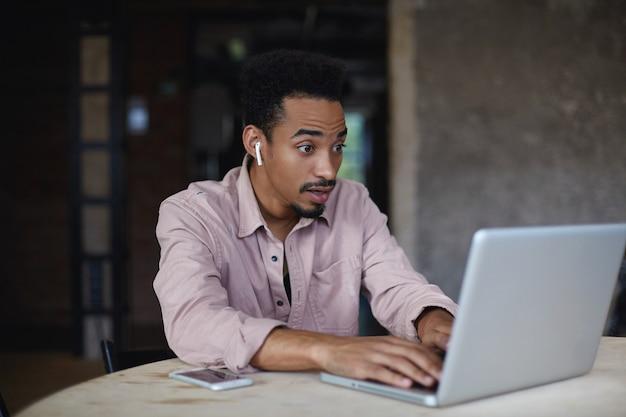Удивленный красивый молодой бородатый мужчина с темной кожей морщит лоб и изумленно поднимает брови, глядя на экран своего современного ноутбука, позируя над интерьером городского кафе