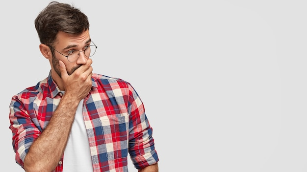 Surprised handsome young male covers mouth with palm, looks with shocked expression aside, notices something strange, dressed in checkered shirt, isolated over white wall. reaction concept