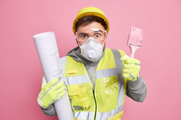 Surprised handyman holds blueprint and paint brush works on construction project plan wears protective helmet mask and glasses uniform
