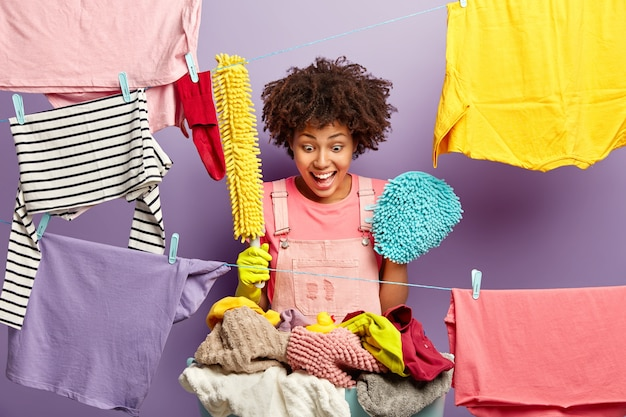 Surprised happy african american housewife holds mop and brush for wiping dust, stares at small rubber duck on pile of laundry left by child, does household chores, busy washing and cleaning.