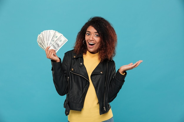 お金を保持している革のジャケットで驚いて幸せなアフリカ女性