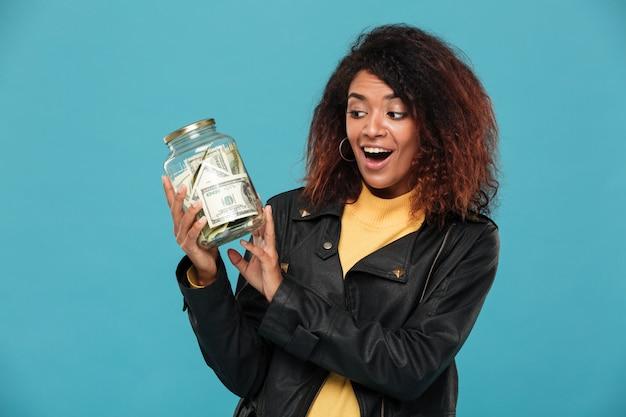 瓶を見て革のジャケットで驚いて幸せなアフリカ女性