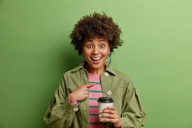 Удивленная счастливая афро-американка указывает на себя и спрашивает, вы выбираете, я не могу поверить в то, что носит модную одежду, пьет кофе на вынос, изолированный над зеленой стеной