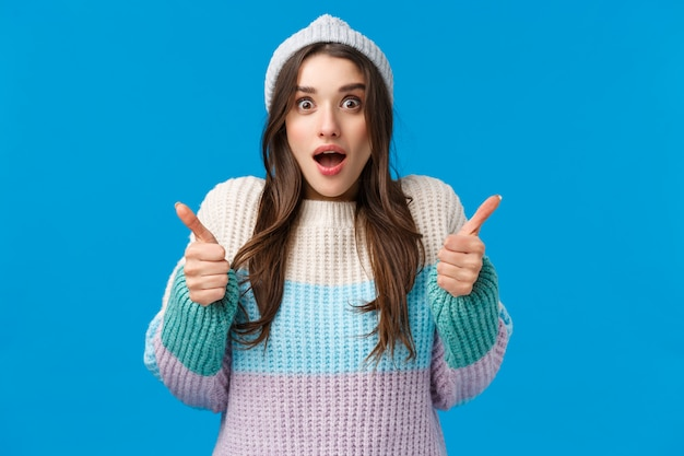 Surprised and happy amazed young brunette woman in winter hat, sweater