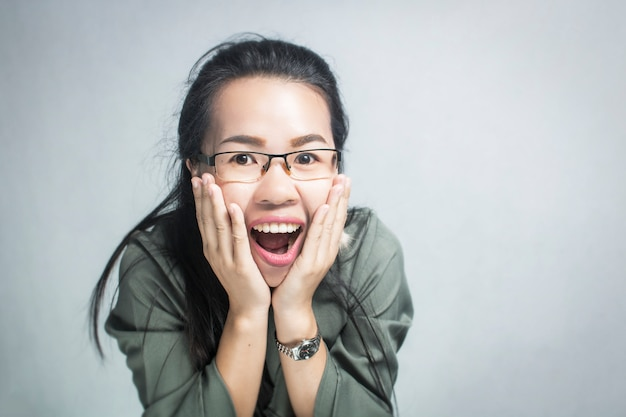 Surprised and happy asian woman wearing glasses on gray background