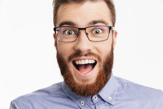 Удивленный счастливый бородатый элегантный мужчина в очках радуется и смотрит