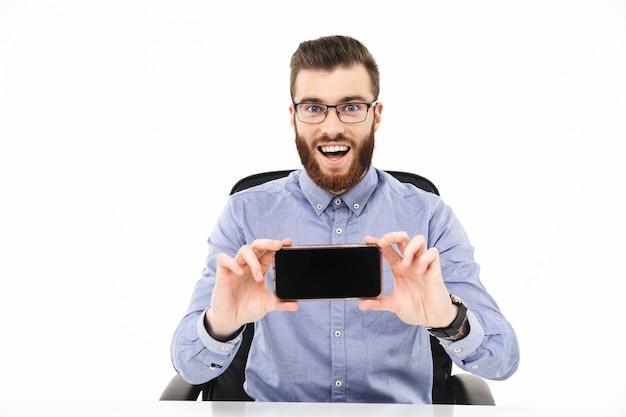 Удивленный счастливый бородатый элегантный мужчина в очках показывает пустой экран смартфона и смотрит на камеру, сидя за столом