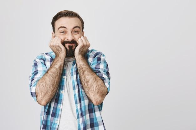 Il ragazzo barbuto felice sorpreso sembra stupito