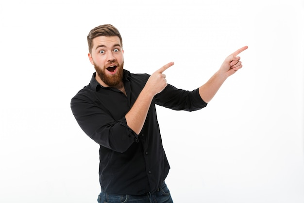 Surprised happy bearded man in shirt pointing away