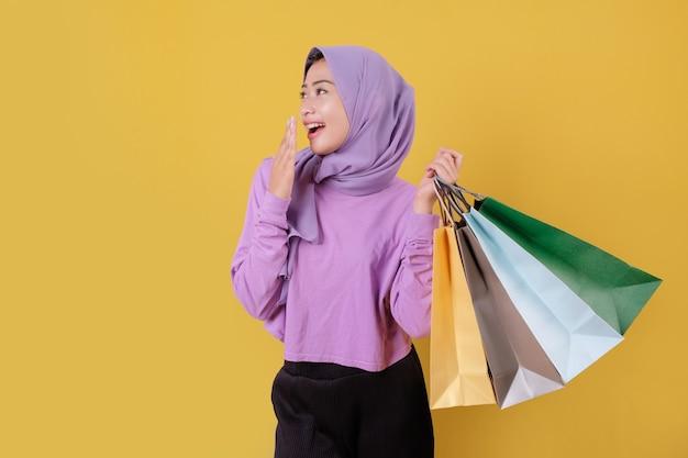 명랑하고 즐거운 쇼핑 가방을 들고 놀란 행복 아름다운 아시아 쇼핑 중독 여성