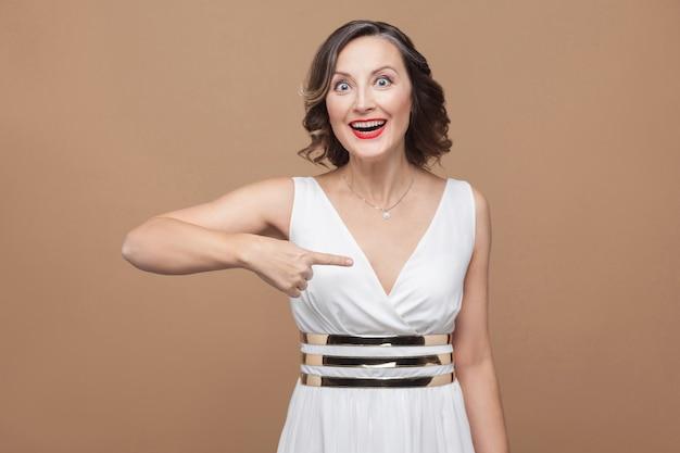 Сама удивленная счастливая красивая женщина указывая пальцем. эмоционально выражающая женщина в белом платье, красных губах и темной вьющейся прическе. студийный снимок, закрытый, изолированный на бежевом или светло-коричневом фоне