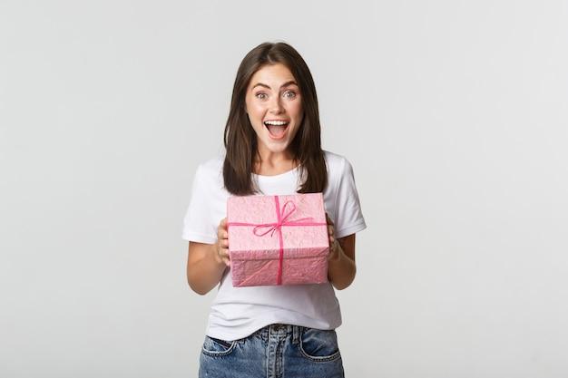 Удивленная девушка с днем рождения получает обернутый подарок, белый.