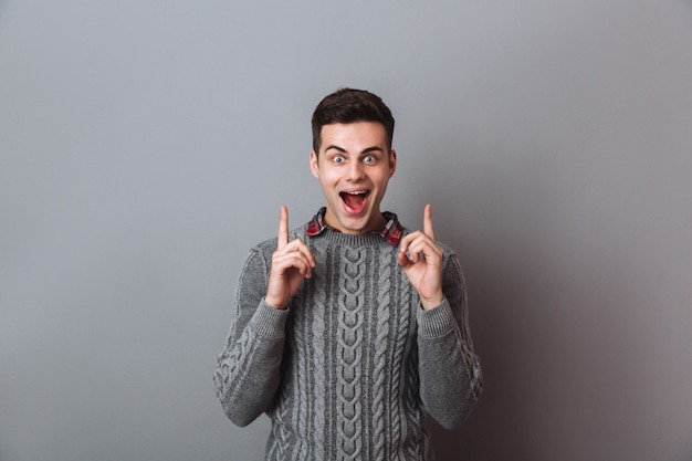 Surprised happy brunette man in sweater pointing up and looking