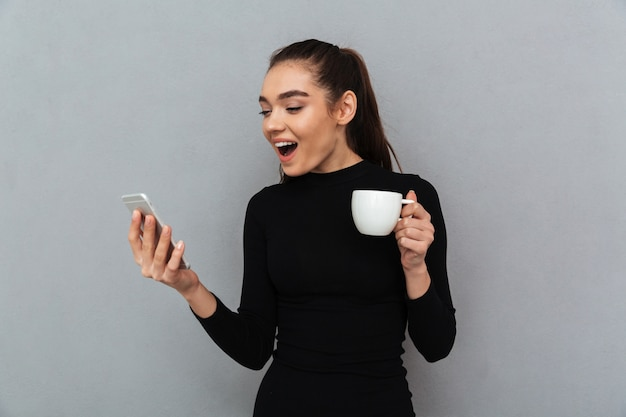 Surprised happy brunette woman in black clothes looking at smartphone