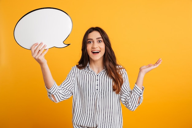 Surprised happy brunette woman in shirt holding blank speech bubble
