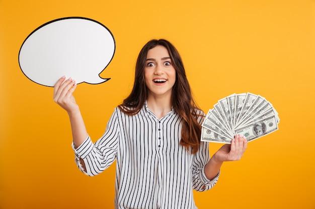 Surprised happy brunette woman in shirt holding blank speech bubble