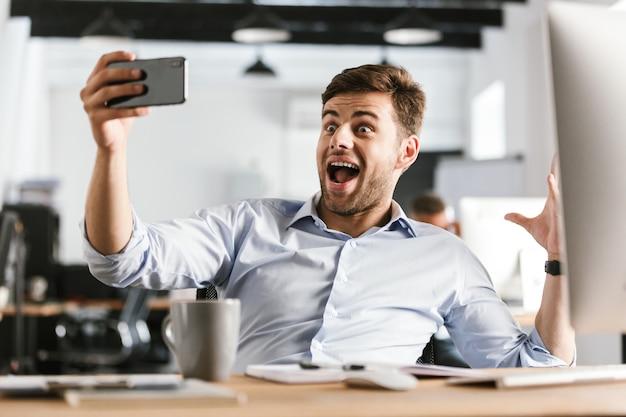 オフィスのテーブルのそばに座ってスマートフォンで自分撮りを作って驚いた幸せなビジネスマン