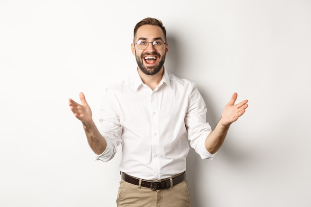 Surprised and happy businessman welcome you, looking excited and smiling, standing against white background.