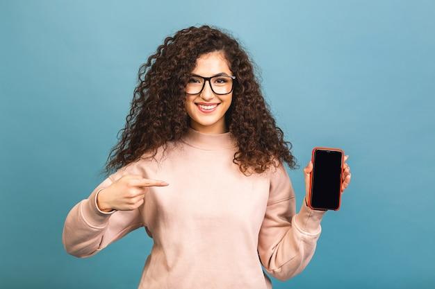 Удивленная счастливая кудрявая брюнетка женщина показывает пустой экран смартфона и указывает на него, глядя в камеру