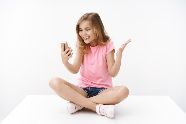 Surprised happy cute blond teenage little b-day girl receive congratulations via video-call, smiling amazed hold smartphone raise hand excited and amused, look mobile phone joyful, white wall