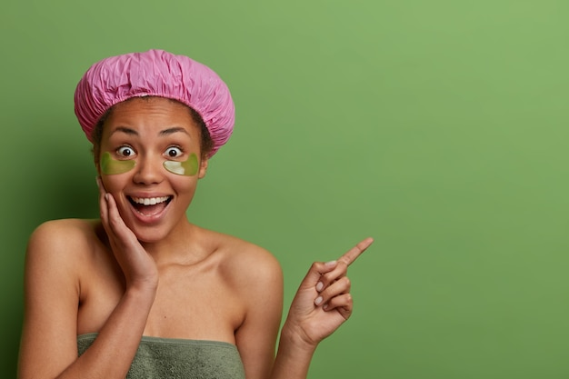 Surprised happy dark skinned woman applies anti aging collagen patches under eyes, shows amazing offer, points aside on blank space, isolated on green wall, wears shower hat, towel around body
