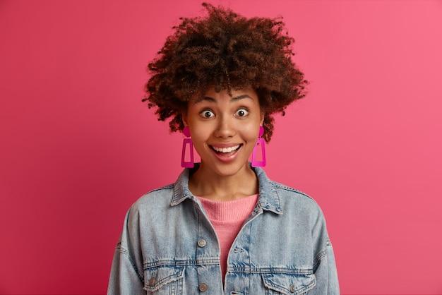 アフロの髪の驚きの幸せな感情的な女性は笑顔で見え、夢が叶うとは信じられない、誰かから素晴らしいプレゼントをもらう、ファッショナブルなデニムの服を着て、ピンクの壁に隔離