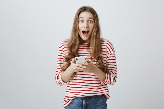 Удивленная счастливая девушка реагирует на классные новости в ленте мобильного телефона
