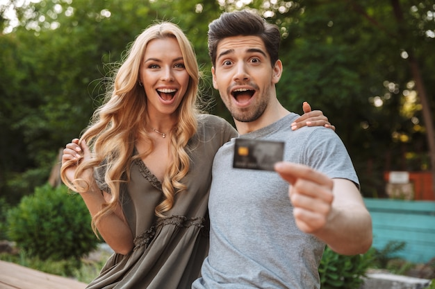 Surprised happy lovely young couple looking at the camera while posing together with credit card outdoors
