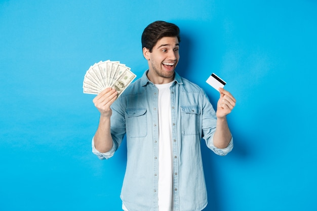 Surprised and happy man looking at credit card and showing money, concept of bank loan, finance and income.