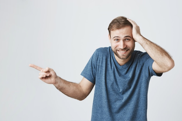 Surprised happy man pointing finger left at banner