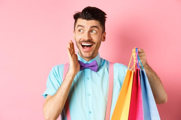 기쁨의 비명을 지르고, 로고를 옆으로보고, 쇼핑백을 들고, 분홍색 위에 서서 놀란 행복 한 사람.