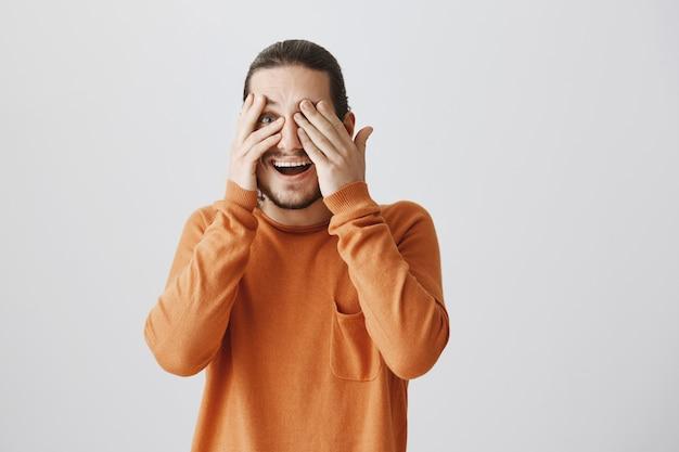 目を閉じて笑って驚いた幸せな男が興奮して指を覗く