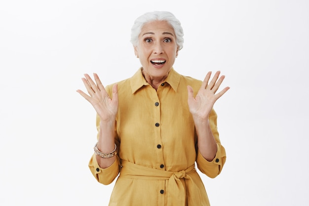 Surprised happy old woman raising hands up and smiling amazed, have good news