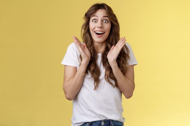 驚いた幸せな感動した縮れ毛の女の子の視線カメラ賞賛満足満足喜び拍手陽気な笑顔広く見えるカメラ魅了された熱狂的な拍手黄色の背景