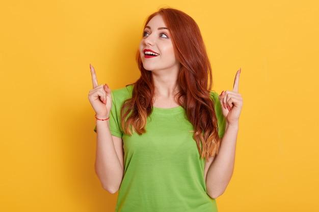 Удивленная счастливая рыжая девушка в повседневной зеленой футболке выглядит удивленно и указывает вверх указательными пальцами, позирует изолированно