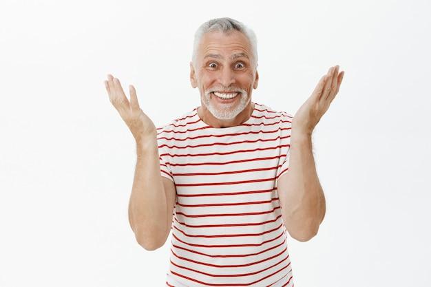 驚いた幸せな年配の男性は、陽気な笑顔で素晴らしいニュースに反応します
