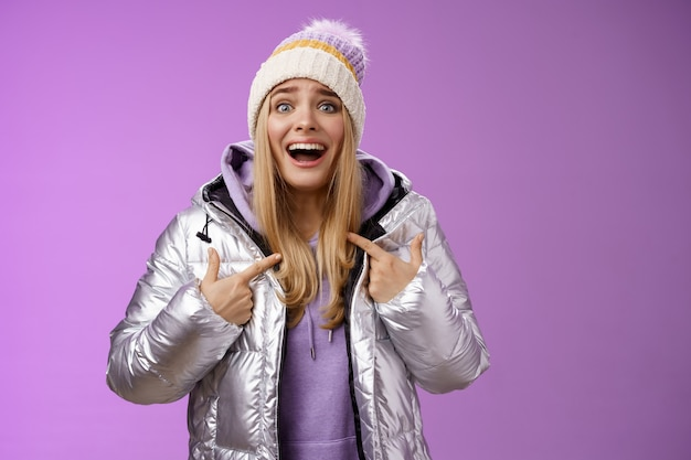 Surprised happy smiling joyful attractive woman pointing herself satisfied picked was chosen winner standing excited in silver shiny jacket winter hat cannot believe own luck, purple background.