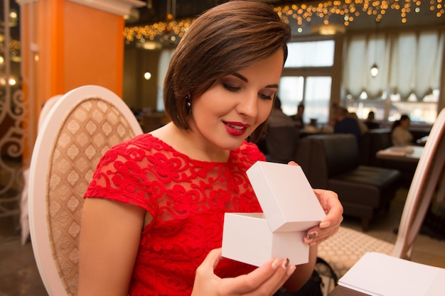 Surprised happy woman sitting by the table on date in cafe and gets the gift.