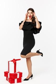 Donna sorpresa e felice in piedi in abito di lusso e labbra rosse, riceve regali per le vacanze e sembra stupita, esultante dai regali, in piedi su sfondo bianco.