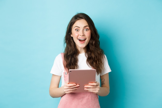 驚いた幸せな女性は驚いてカメラを見つめ、驚くべきニュースを聞き、タブレットを手に持って、青い背景の上に立っています。