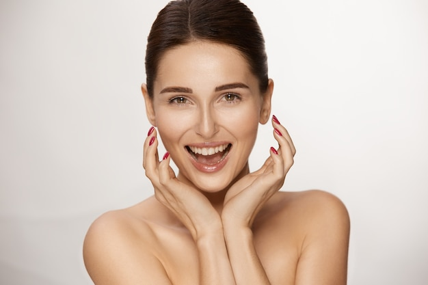 Surprised and happy woman with fresh skin and shiny hair, lovely woman with beautiful smile and naked shoulders
