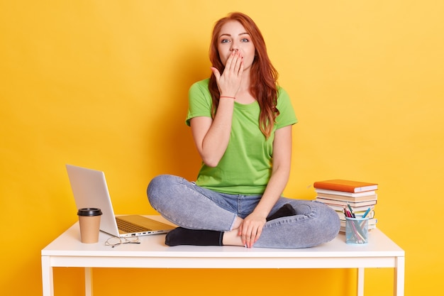 驚いた幸せな若い女の子、予期しない勝利や成功を信じられない、手のひらで口を覆っている、緑のtシャツとジーンズを着ている、黄色のスタジオの壁にポーズ