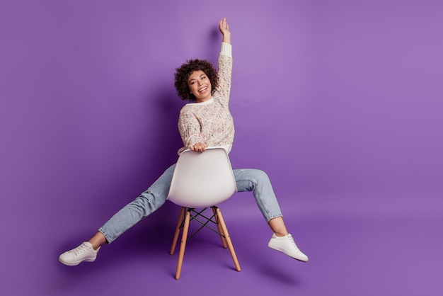 Surprised happy young woman face in excitement raise hand have fun sit chair isolated on purple background