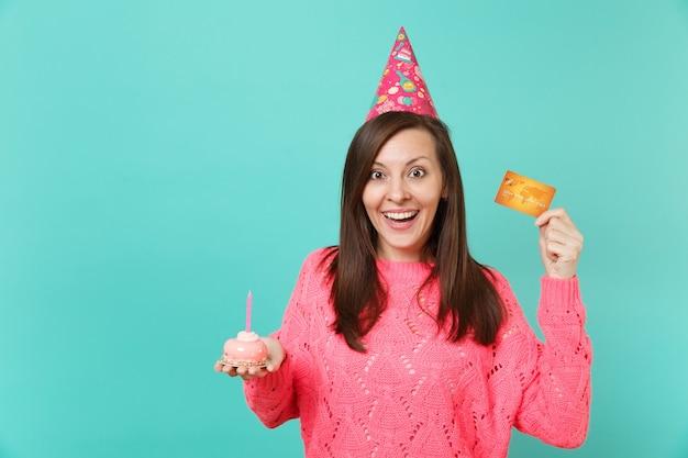 분홍색 스웨터를 입은 행복한 젊은 여성, 파란색 청록색 벽 배경에 격리된 촛불 신용 카드가 있는 손 케이크를 들고 있는 생일 모자. 사람들이 라이프 스타일 개념입니다. 복사 공간을 비웃습니다.