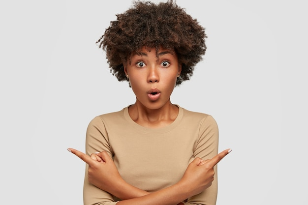 Surprised hesitant dark skinned female has stunned facial expression, points with both index fingers at different sides or directions, shows you product, wears casual beige sweater, isolated on white