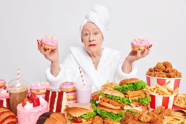 Surprised hesitant woman pensioner  holds two delicious glazed doughnuts surrounded by harmful food high in calories