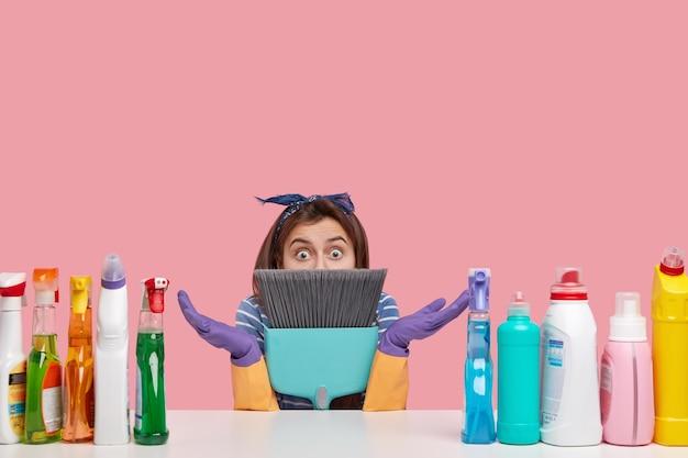 Удивленная нерешительная молодая домохозяйка прячется за метлой в недоумении пожимает плечами, широко открывает глаза, носит повязку на голову.
